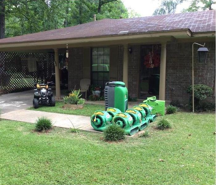 SERVPRO fans and dehumidifiers sitting on the sidewalk in front of a brick home