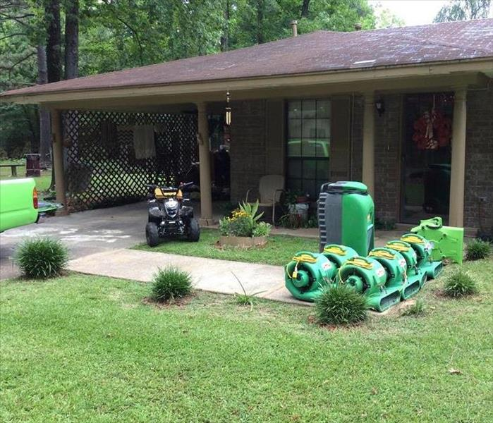 SERVPRO equipment lined up on the sidewalk in front of a home.