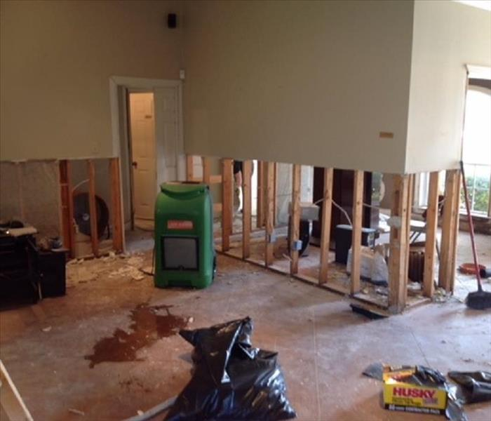 Flood damaged home showing flood cuts, debris in garbage bag, and SERVPRO drying equipment
